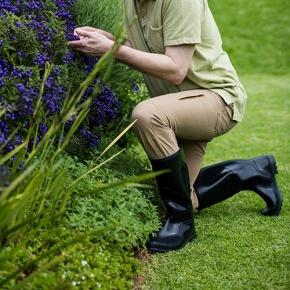 Person-Kneeling-On-Grass-In-Garden